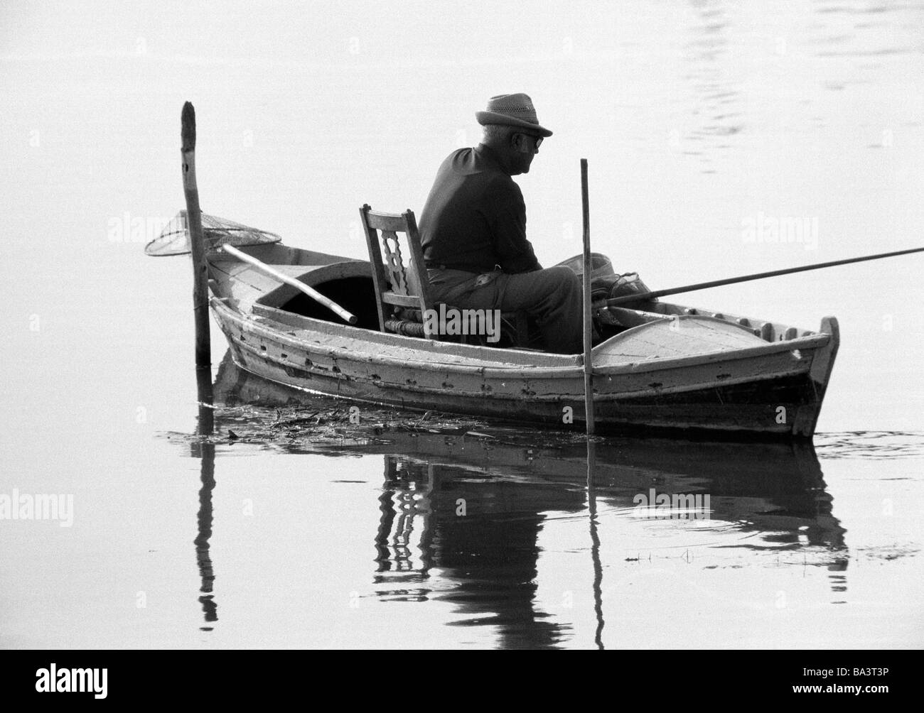 Seventies, black and white photo, hobby, fishing, angler sits in a boat casting for fish, backlight, silhouette, - Stock Image