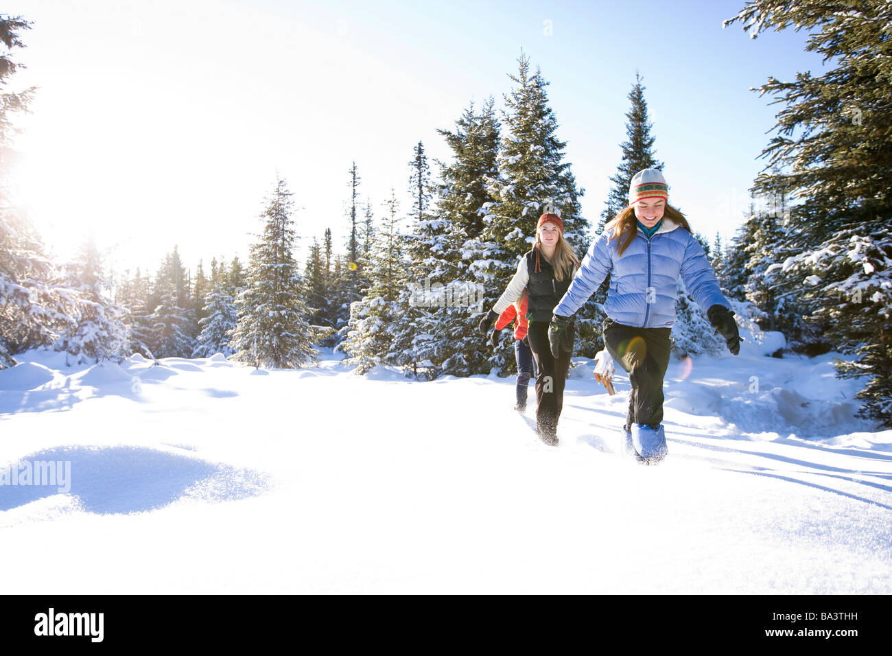 Three young women on snowshoes enjoy the outdoors near Homer Alaska during winter - Stock Image
