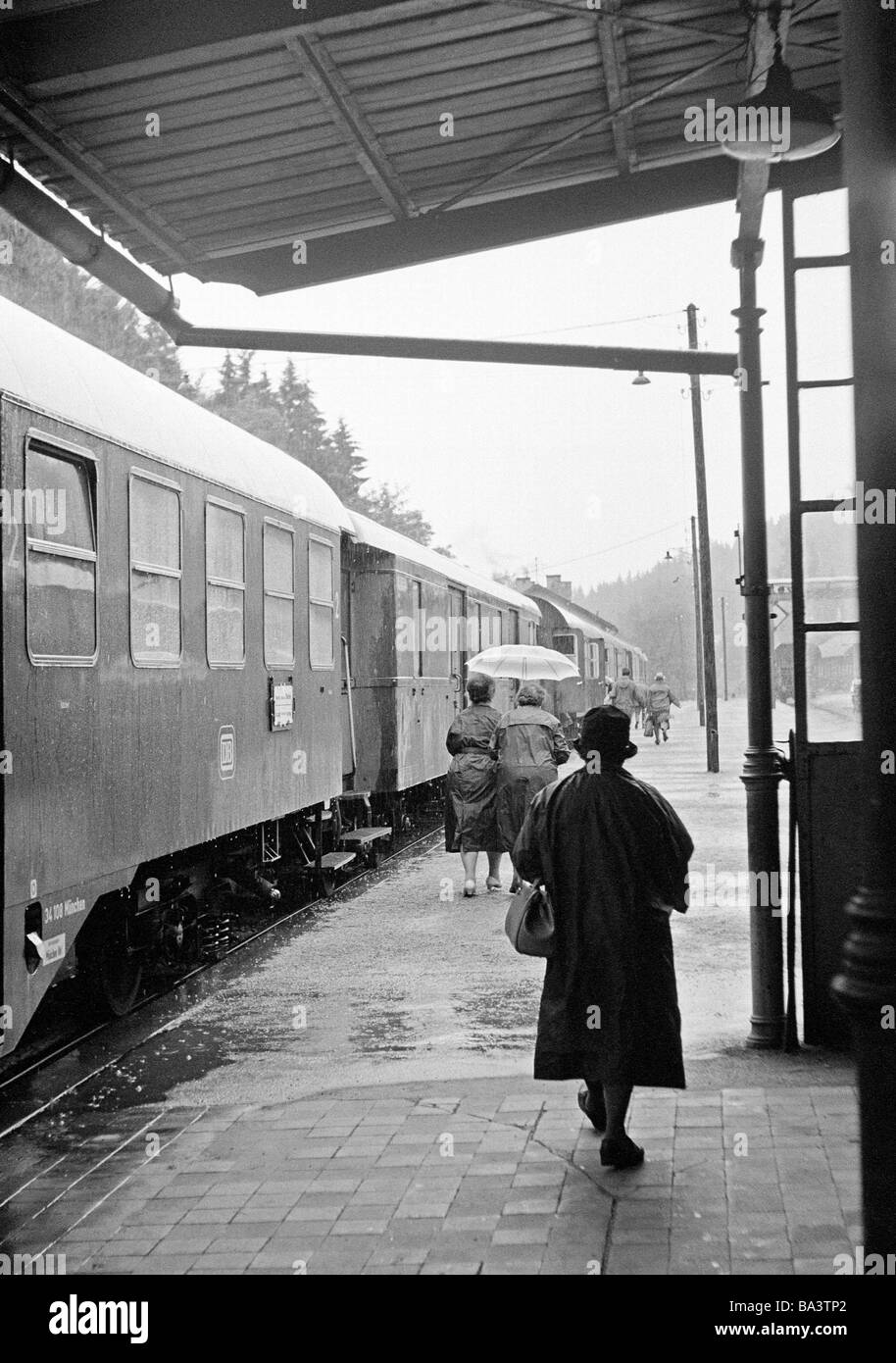 Sixties, black and white photo, people, senior, older woman walks on a platform to the waiting train, station, coat, - Stock Image