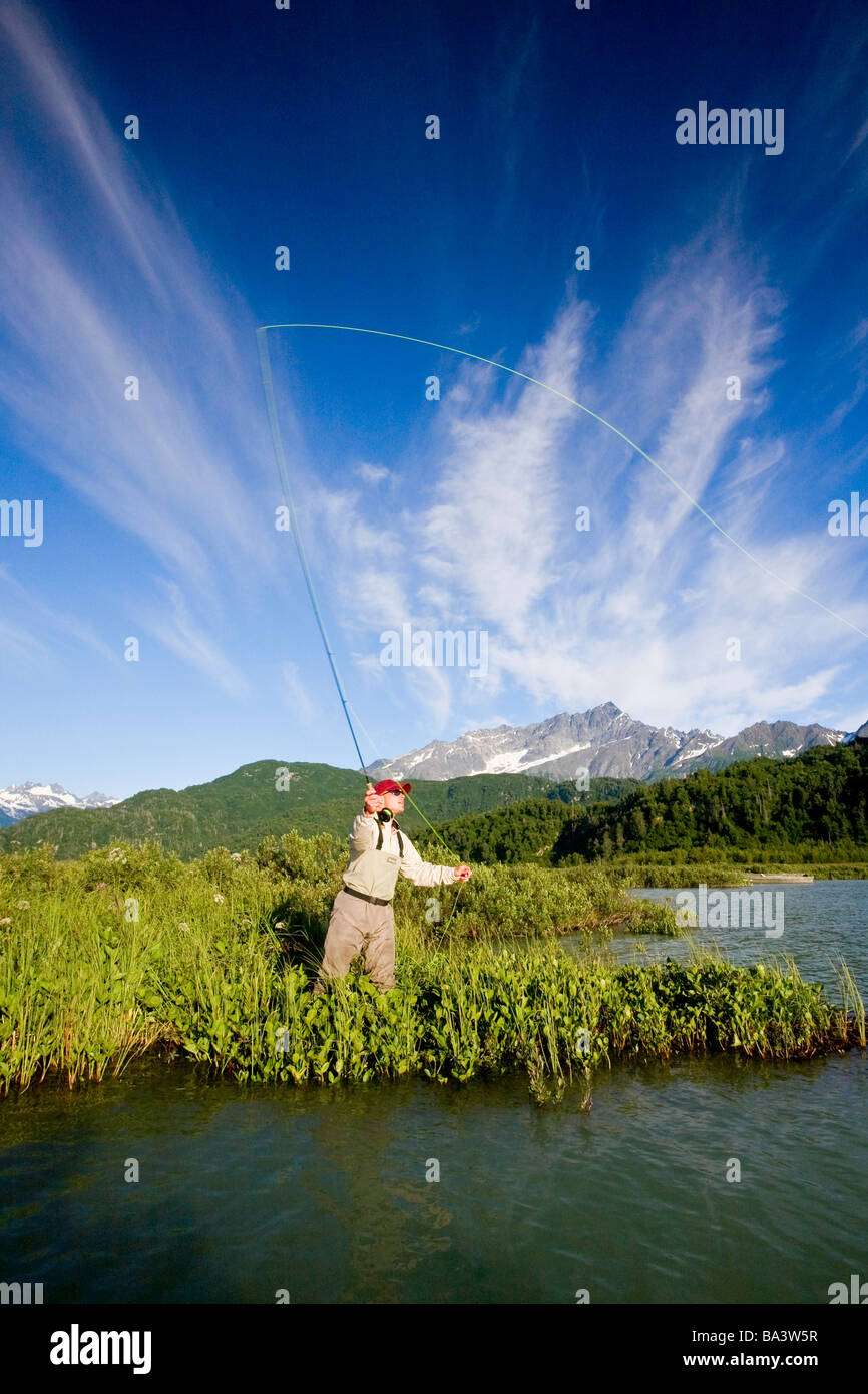 Man fly-fishing for salmon on Big River Lakes with Chigmit Mountains in the background in Southcentral Alaska during - Stock Image