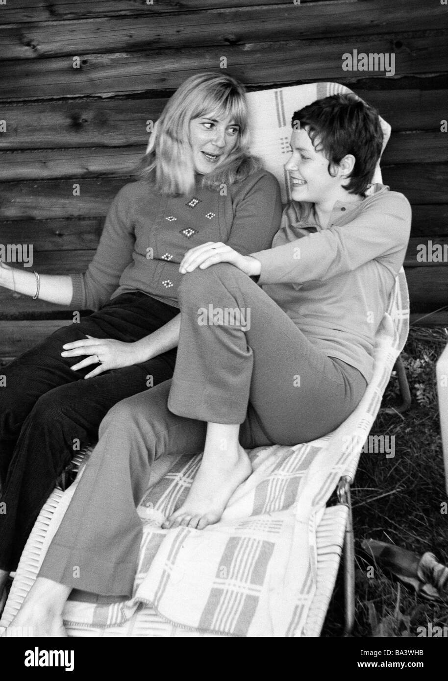 Seventies, black and white photo, people, two young girls sitting side by side, talking, pullover, trousers, aged - Stock Image