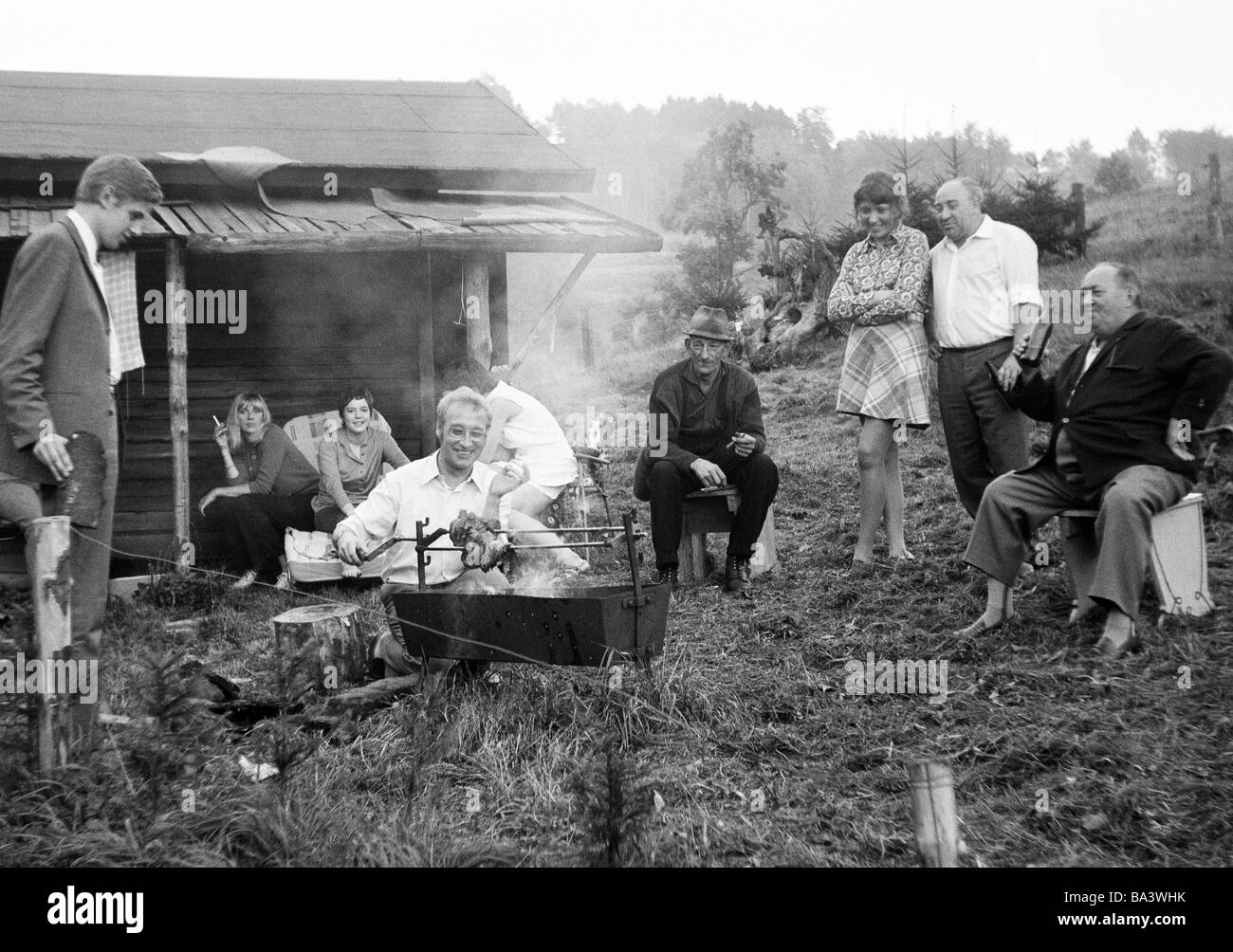 Seventies, black and white photo, people, freetime, barbecue, young man turns a roast on the charcoal grill, young - Stock Image