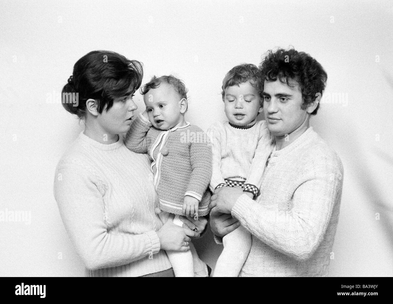 Seventies, black and white photo, people, young family with two children, mother carries daugther on her arms, father Stock Photo
