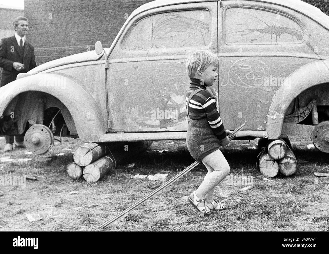 Seventies, black and white photo, people, children, little boy rides on a stick, playing, aged 3 to 4 years, in - Stock Image