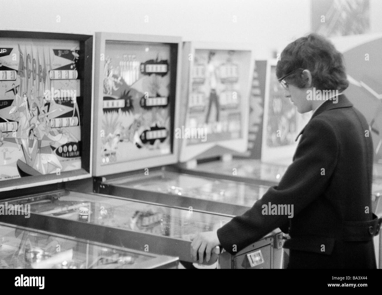 Seventies, black and white photo, people, young boy plays at a pinball machine, gambling hall, gambling hell, freetime, - Stock Image