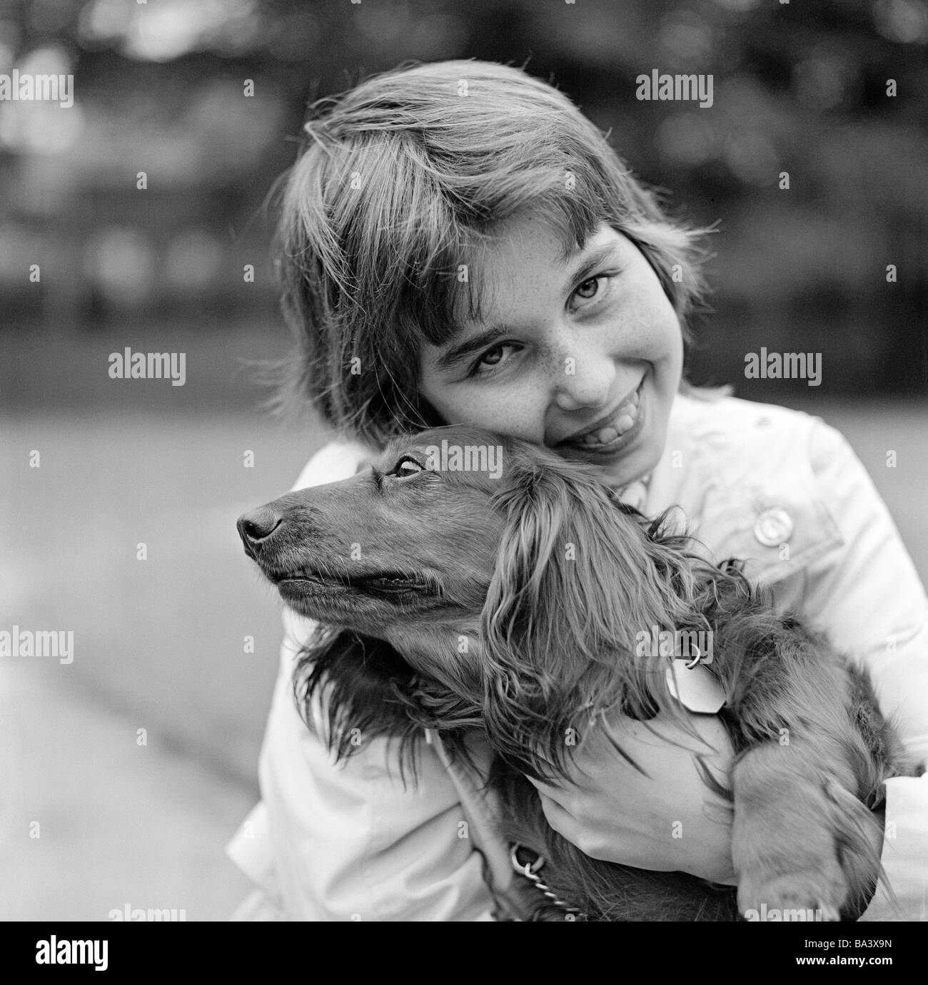 Seventies, black and white photo, human and animal, young girl cuddles with a dachshund, aged 10 to 14 years, domestic - Stock Image