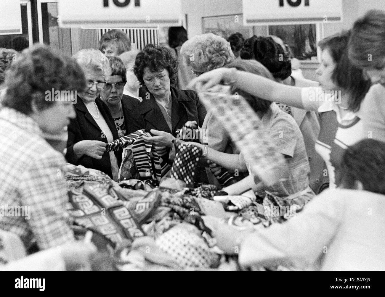 Seventies, black and white photo, people on shopping expedition, closing out sale, several women search for bargains - Stock Image