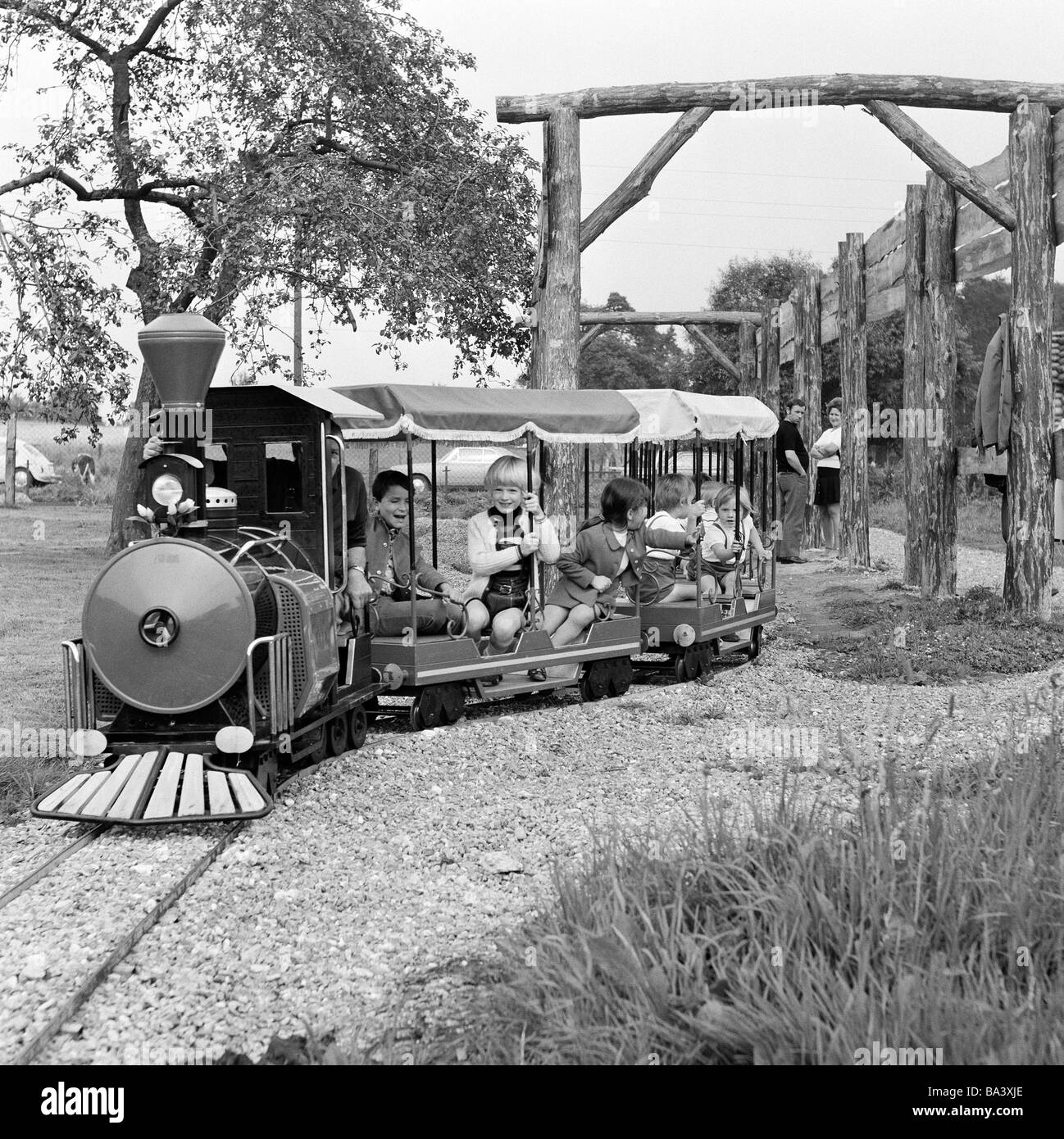 Seventies, black and white photo, people, children, boys and girls drive by a model railway, childrens playground, - Stock Image