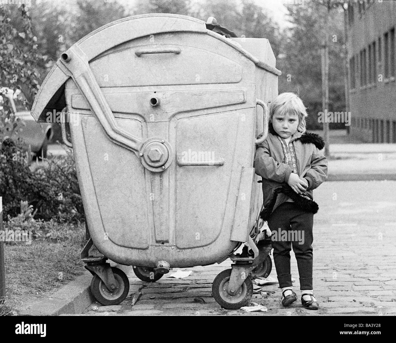 Seventies, black and white photo, people, children, little girl stands near a refuse container, aged 4 to 6 years Stock Photo