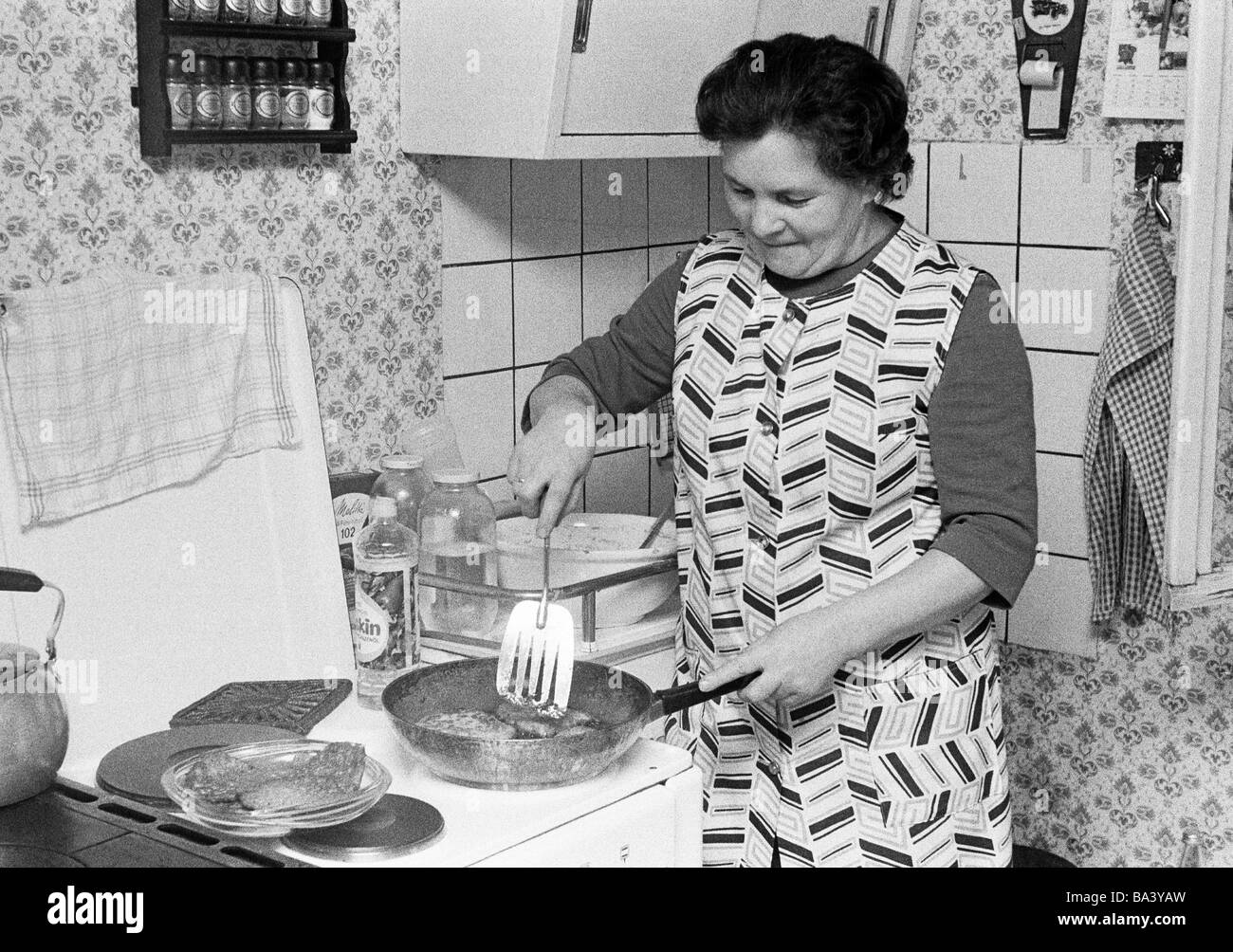 Seventies, black and white photo, people, older woman stands at the cooking-stove and prepares the food, aged 55 - Stock Image