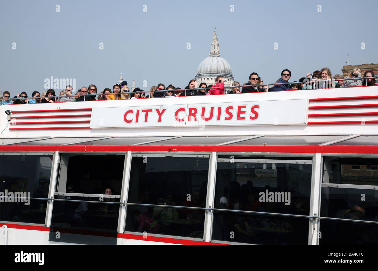 Passengers on River Thames cruise with St Paul's in background - Stock Image