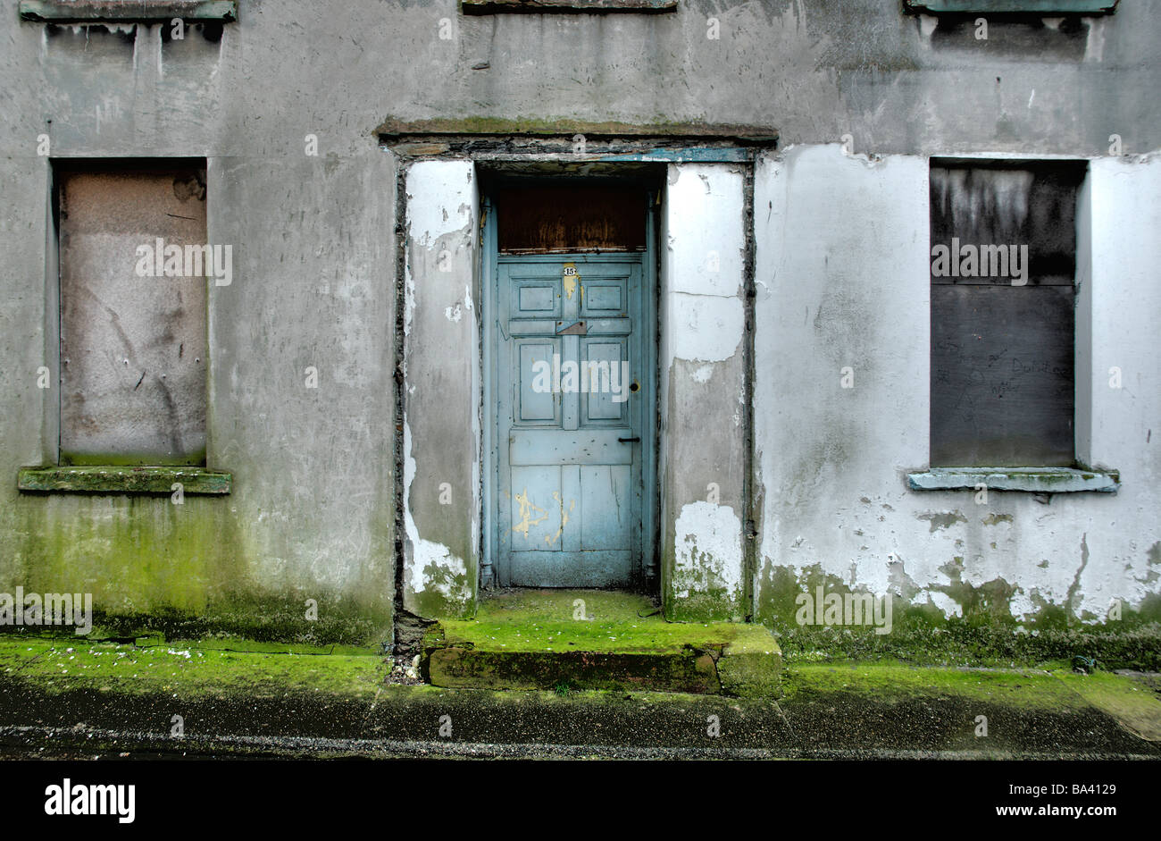 Derelict house with moss growing on pavement - Stock Image