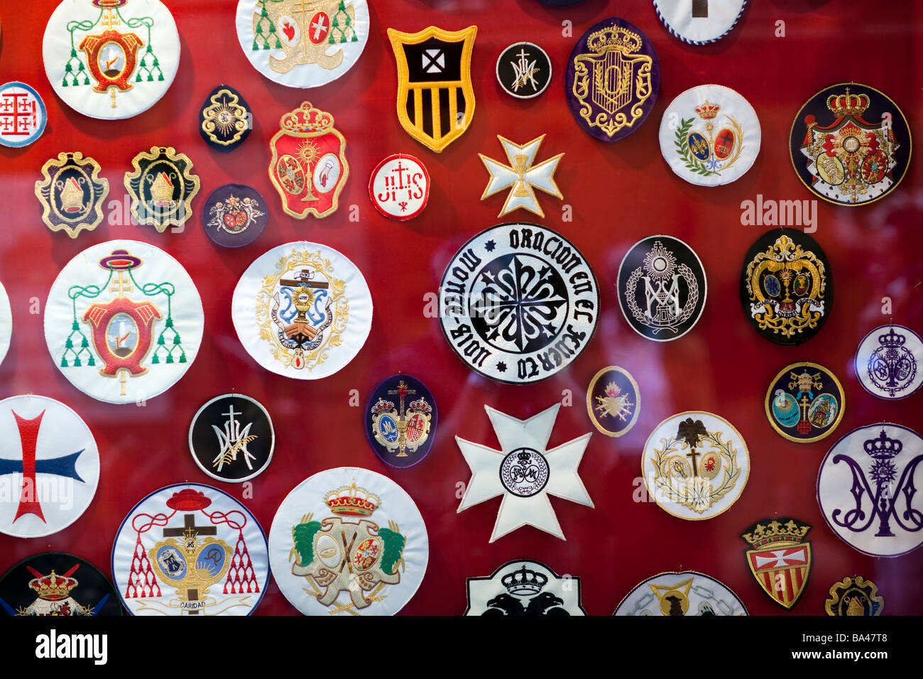 Emblems of Holy Week brotherhoods for sale on a shop window town of Seville autonomous community of Andalusia southern - Stock Image