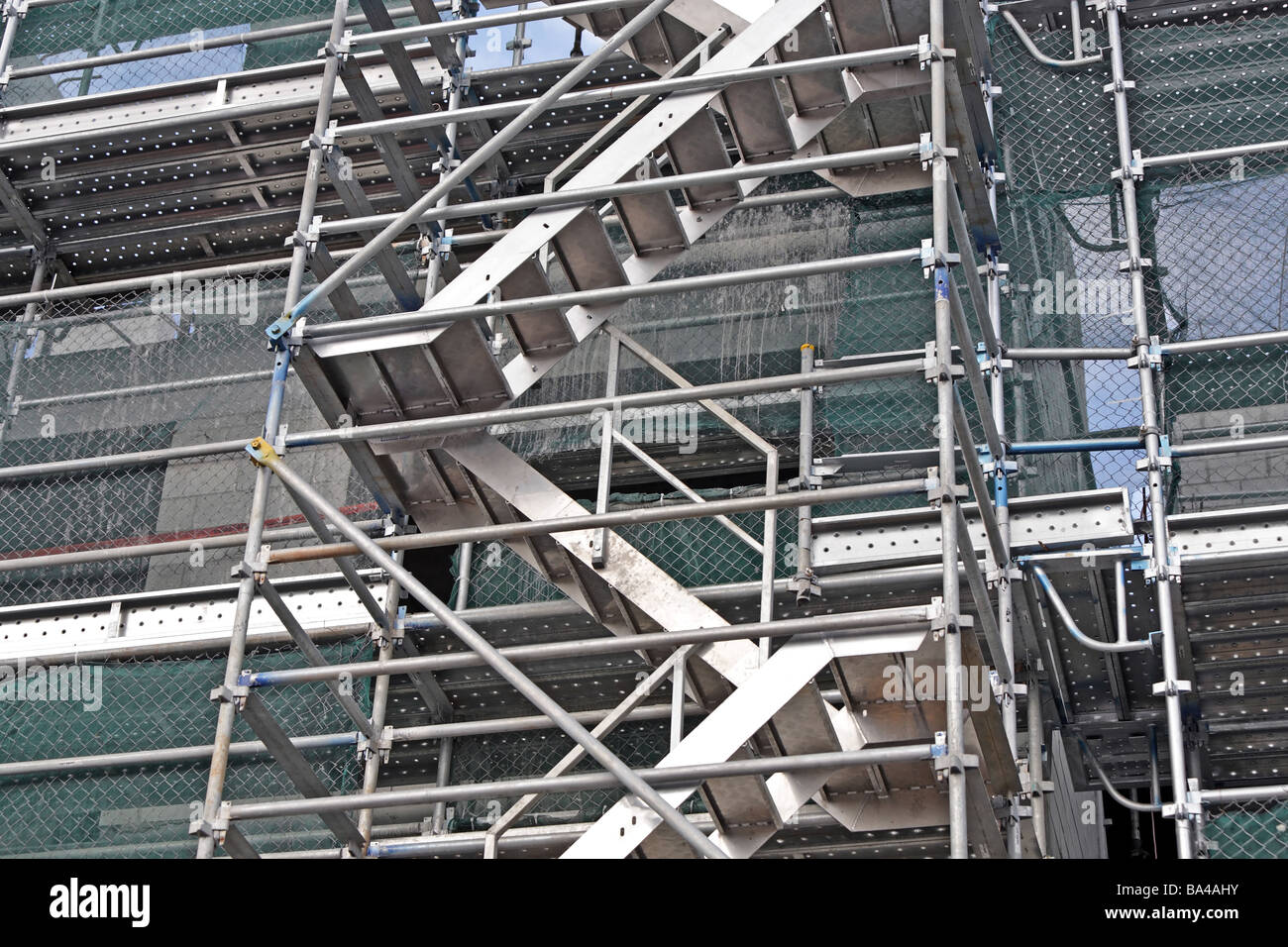 Building Construction Showing Scaffolding Access Stairs And Protective  Netting   Stock Image