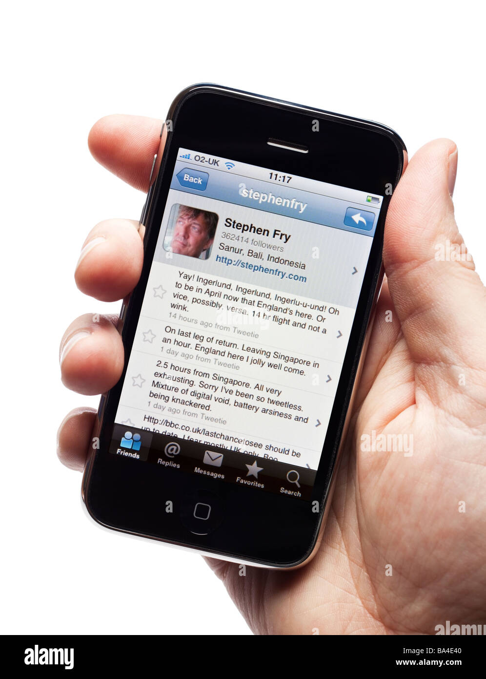 Male hand holding iPhone showing tweets of Stephen Fry a prolific celebrity Twitter fan - Stock Image