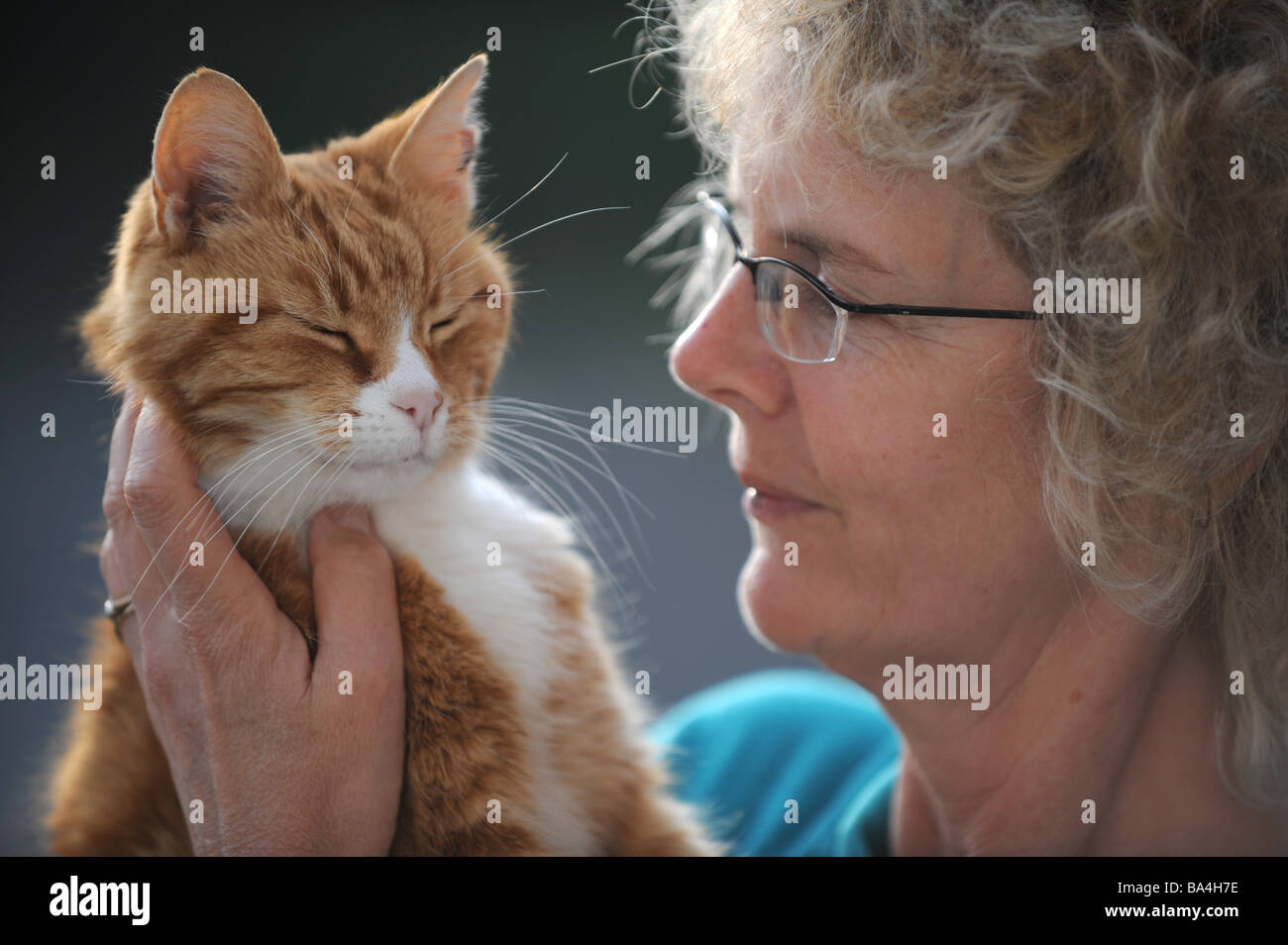 old ginger cat with white face markings and a damaged ear being held by blonde woman april 2009
