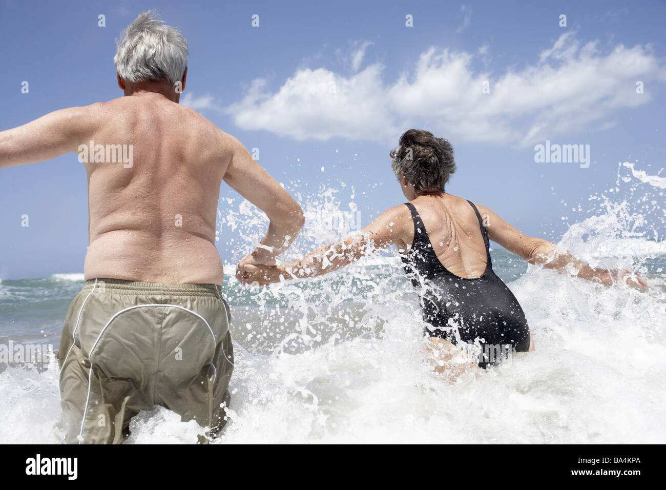 Sea surf senior-pair bath-clothing hand in hand water runs back-opinion detail series people seniors pair 60-70 - Stock Image