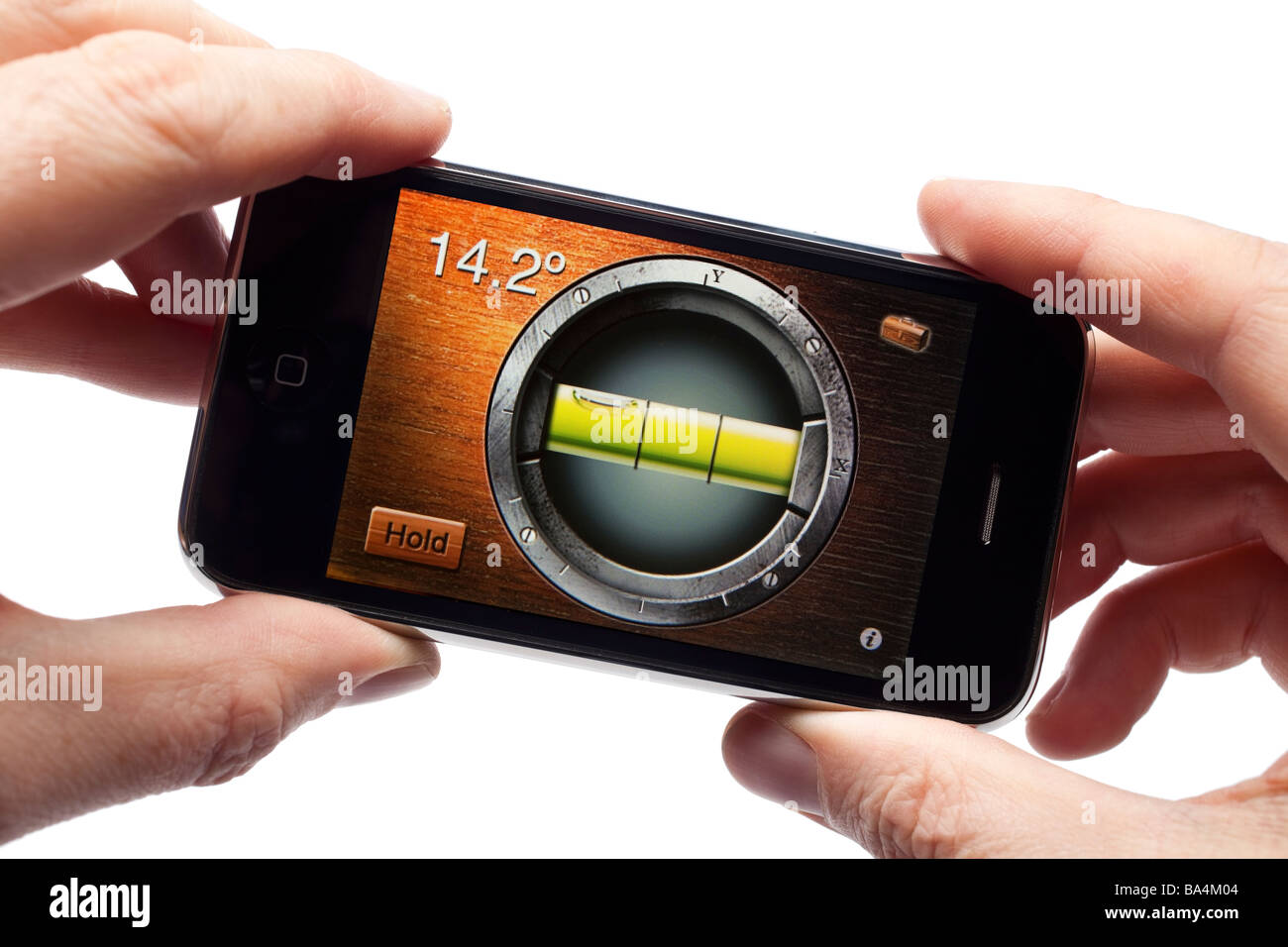 Male hands holding iPhone smartphone smart phone mobile phone using a spirit level application - Stock Image