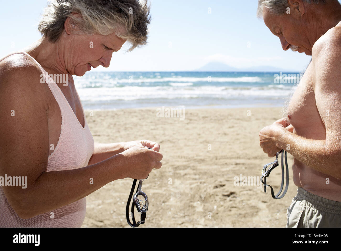 Beach senior-pair bath-clothing swimming-glasses side-portrait broached series people seniors pair 60-70 years beach - Stock Image