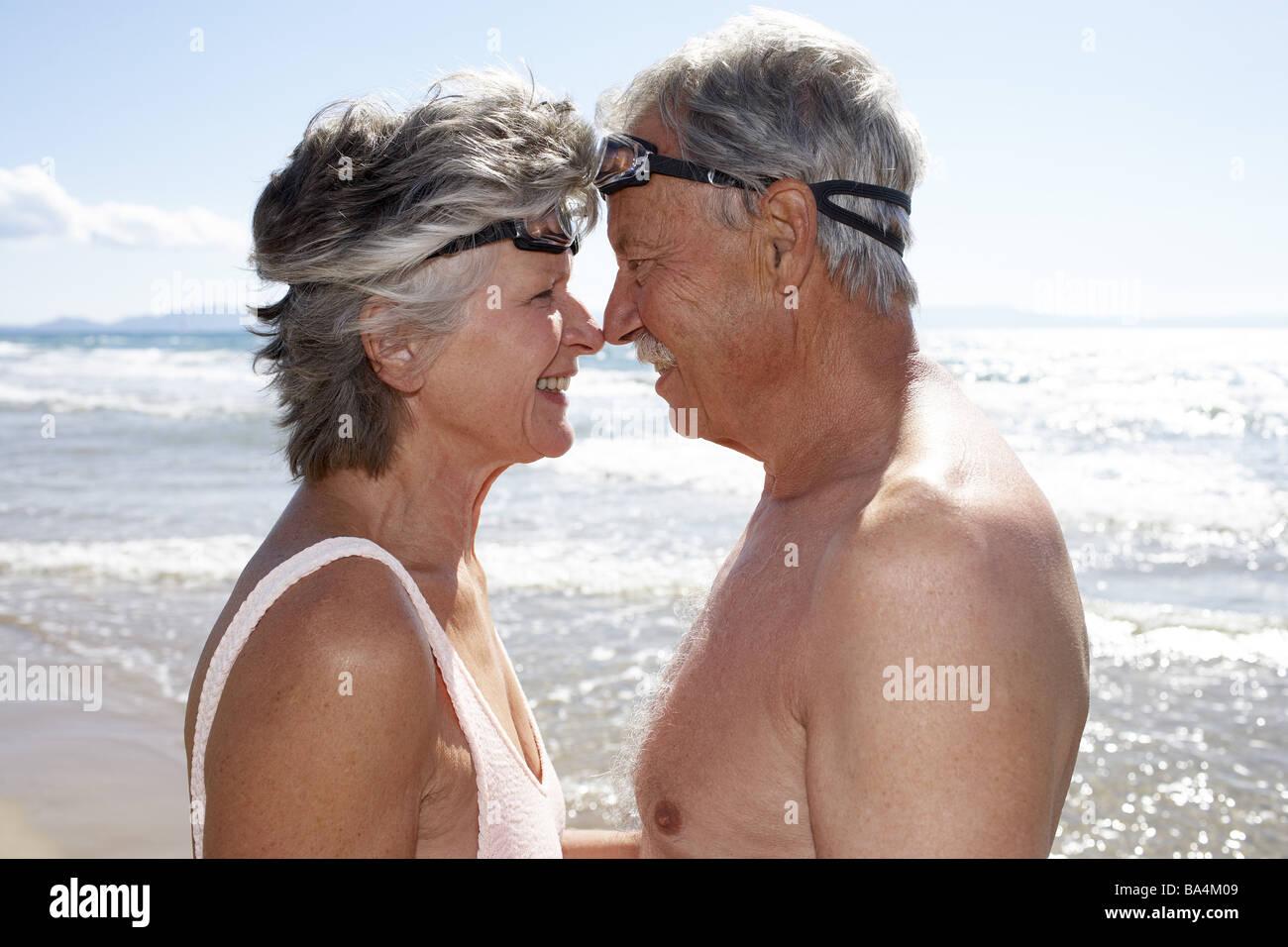 Beach senior-pair bath-clothing swimming-glasses gaze-contact smiles side-portrait back light series people seniors - Stock Image