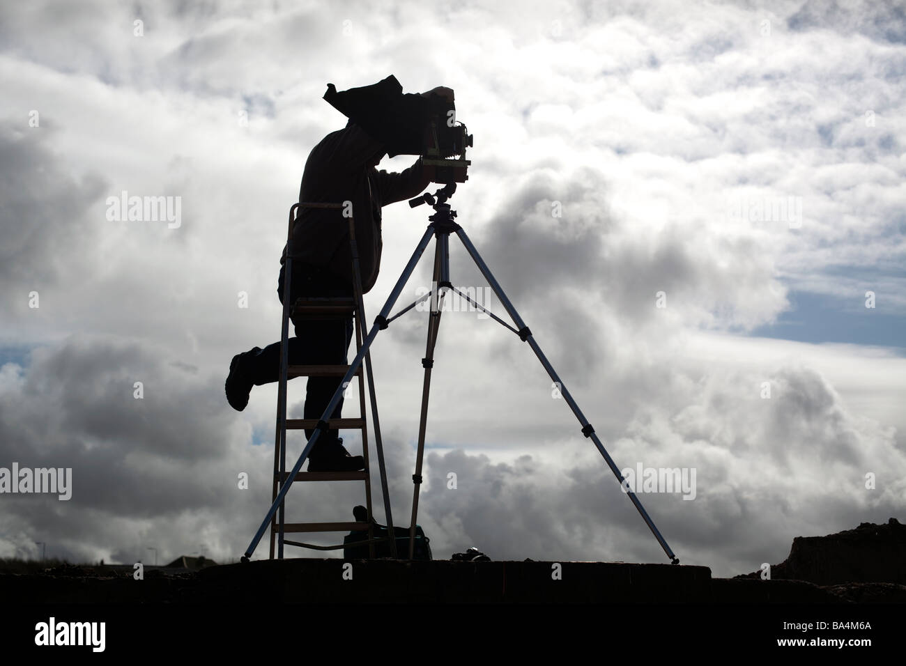 A photographer using a large format camera on a tripod - Stock Image
