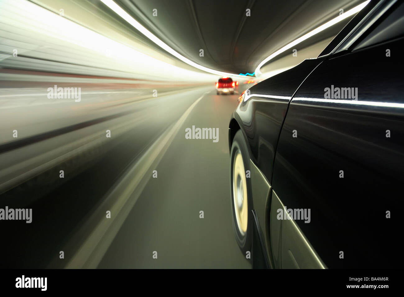 Blurred motion image of cars driving through tunnel - Stock Image