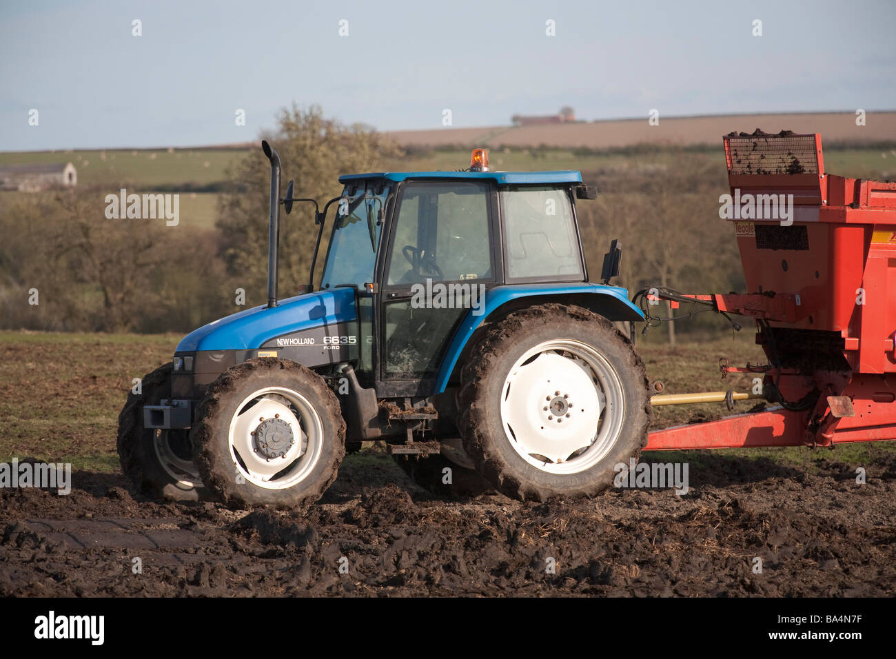 Ford New Holland 6635 tractor and Teagle Rear Discharge Muck Spreader in a field in Warwickshire England UK - Stock Image