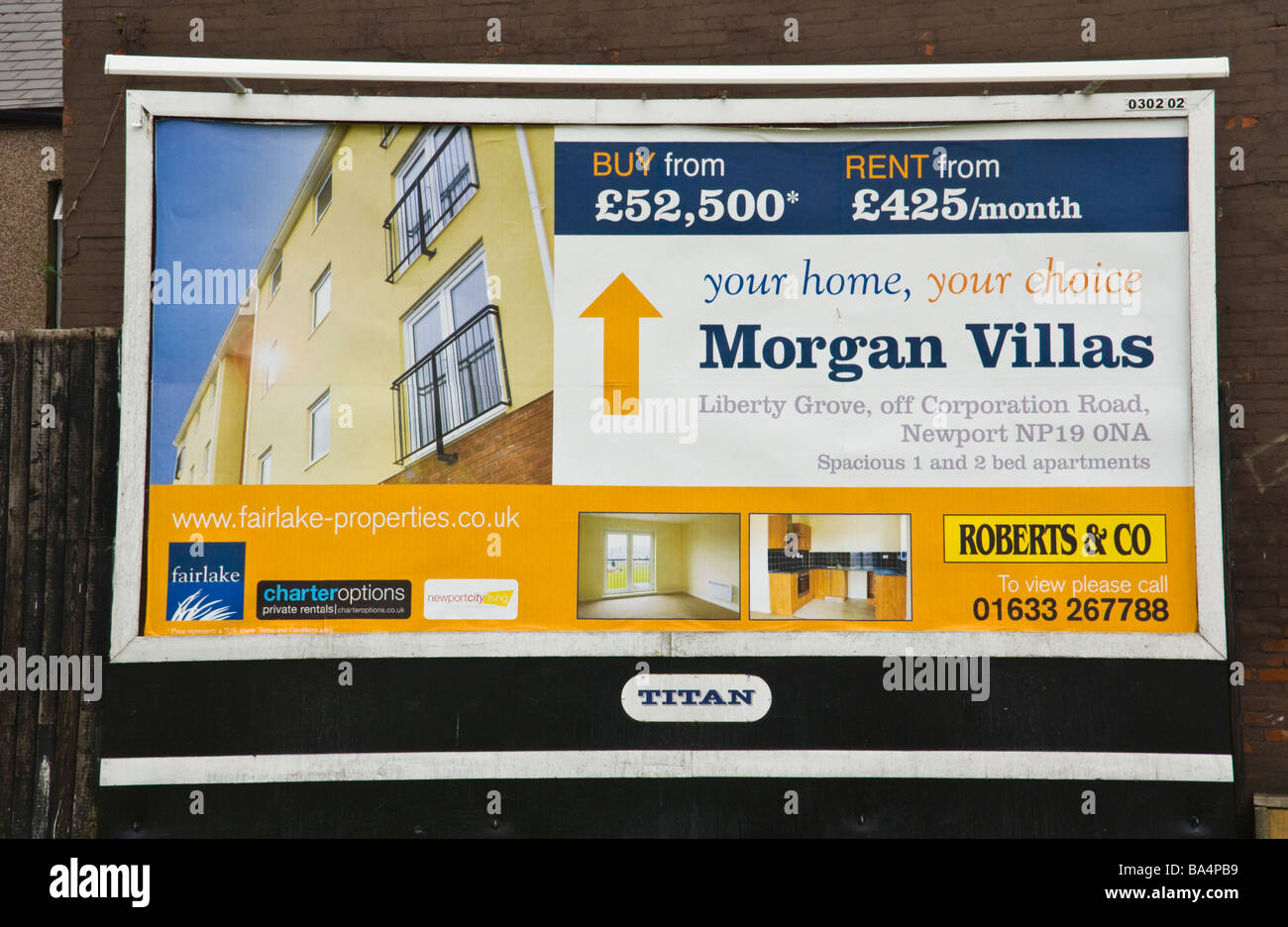 Titan billboard site advertising local house sales on hoarding in Newport South Wales UK - Stock Image