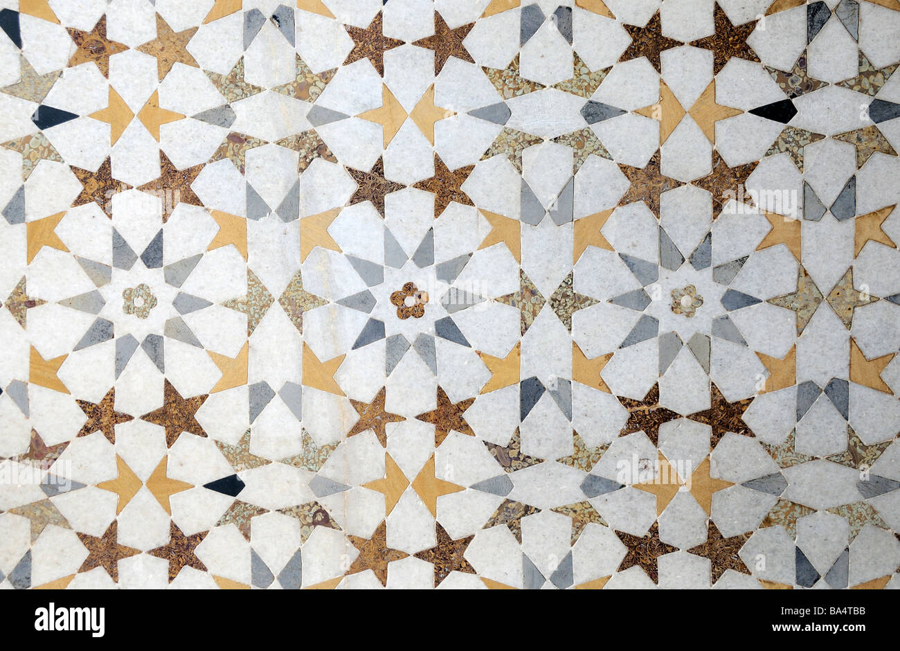 A floor made of a repeating pattern of regular shapes made from semi precious stones inlaid in white marble. Stock Photo