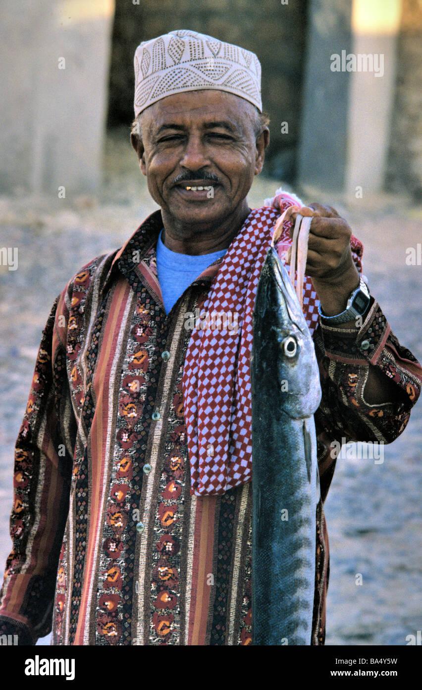 Yemeni Man Wearing Islamic Hat Returning from Market with a Large Fish, Hadibu, Socotra or Suqutra, Yemen - Stock Image