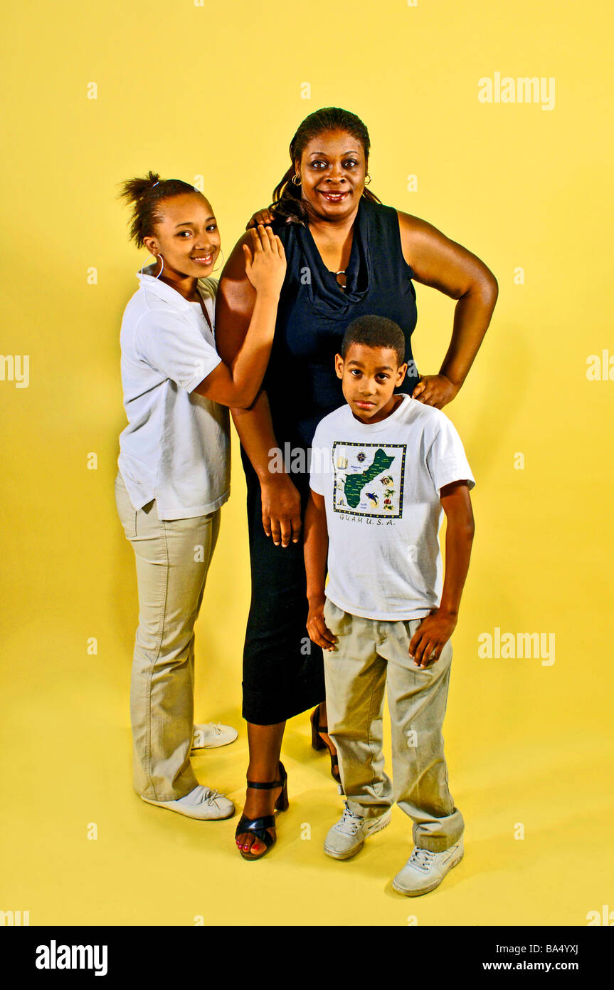 Ethnic single parent guardian poses with two child dependents on a bright yellow background