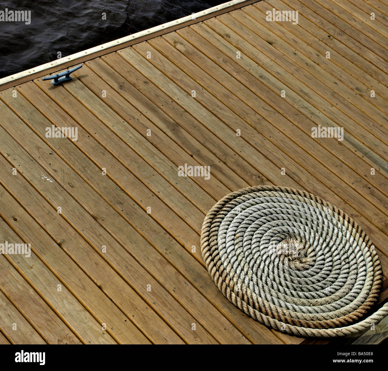 wooden deck on river with coiled rope and tie-up hook, deck is multiple boards and geometric against circle of the - Stock Image