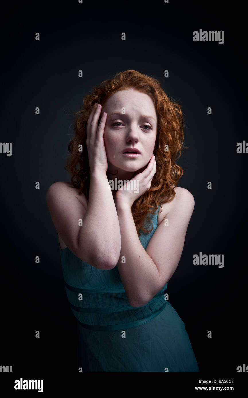 sad red haired woman girl crying alone UK, looking upset tearful, holding her head in her hands - Stock Image