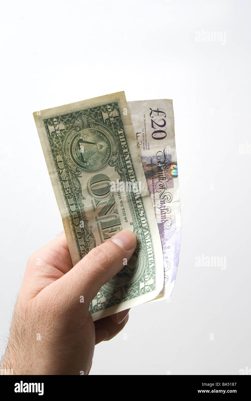Hand holding an American one dollar bill and a twenty pounds British banknote - Stock Image