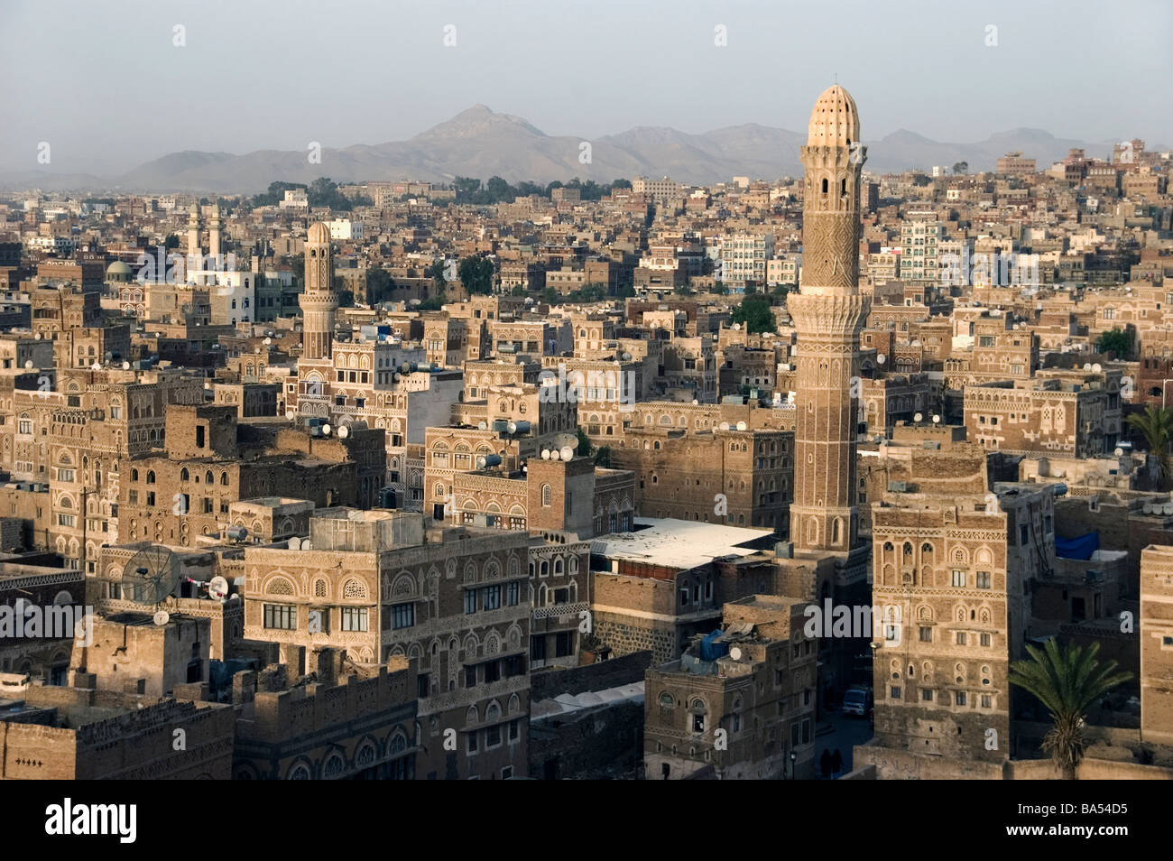 A minaret and traditional tower houses on the skyline of the old city of Sana'a, Yemen. Stock Photo