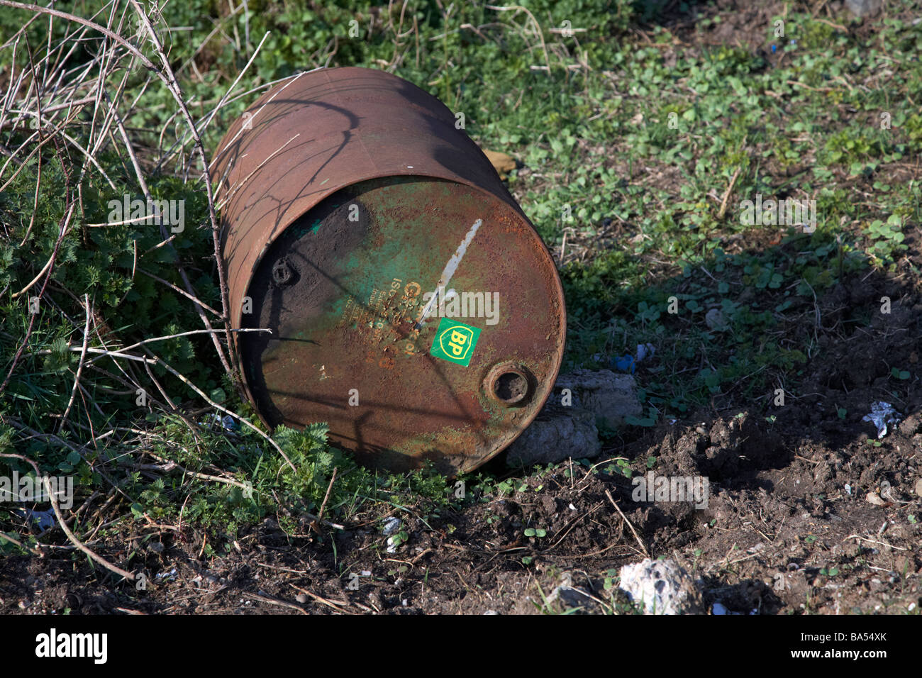 empty rusted discarded bp oil drum in countryside uk - Stock Image