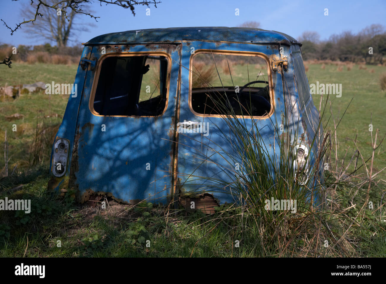 old blue rusted abandoned wreck of an old mini van in a field in county armagh northern ireland uk Stock Photo