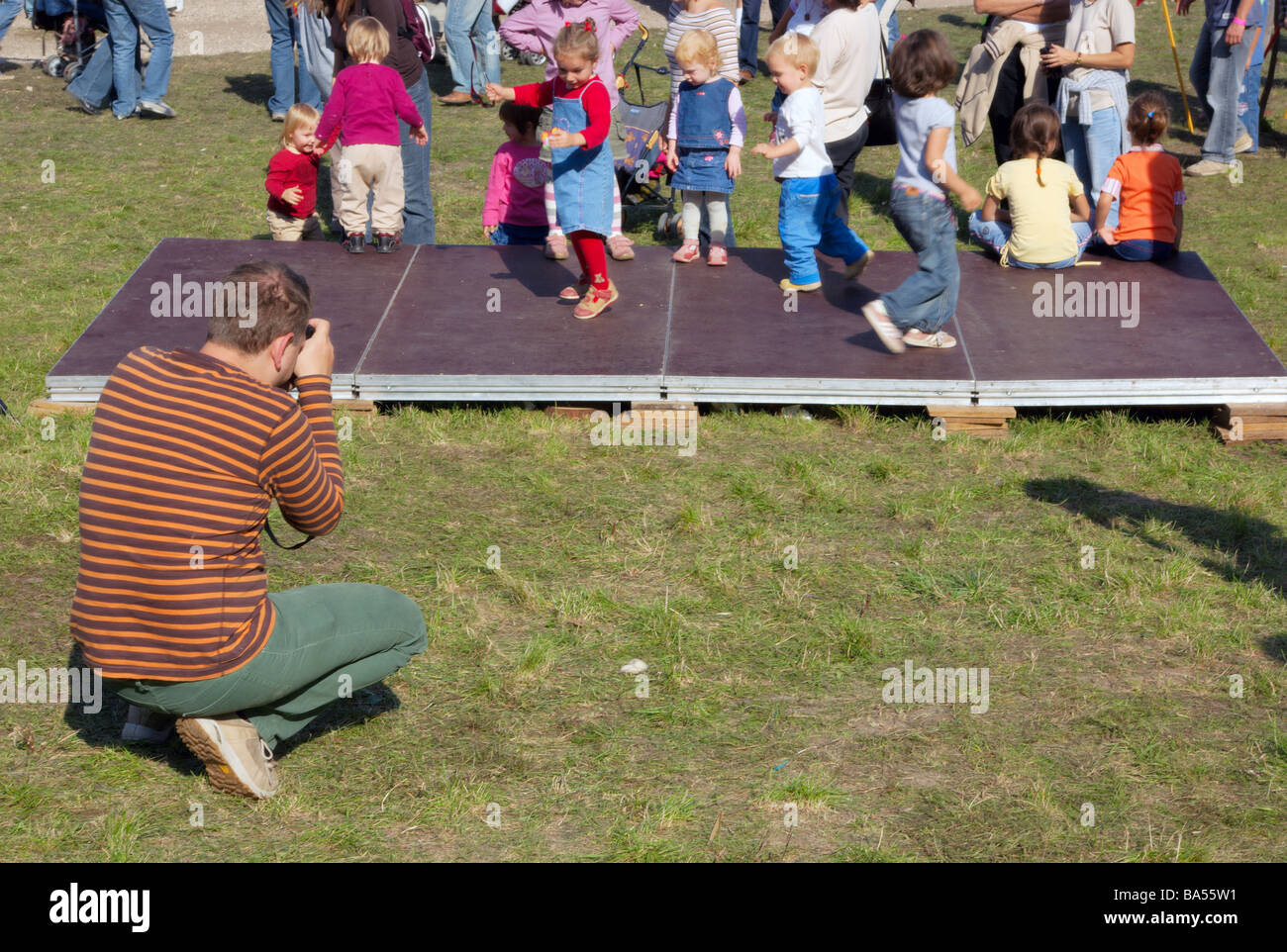 Man photographing children dancing at Hungarian summer festival Stock Photo