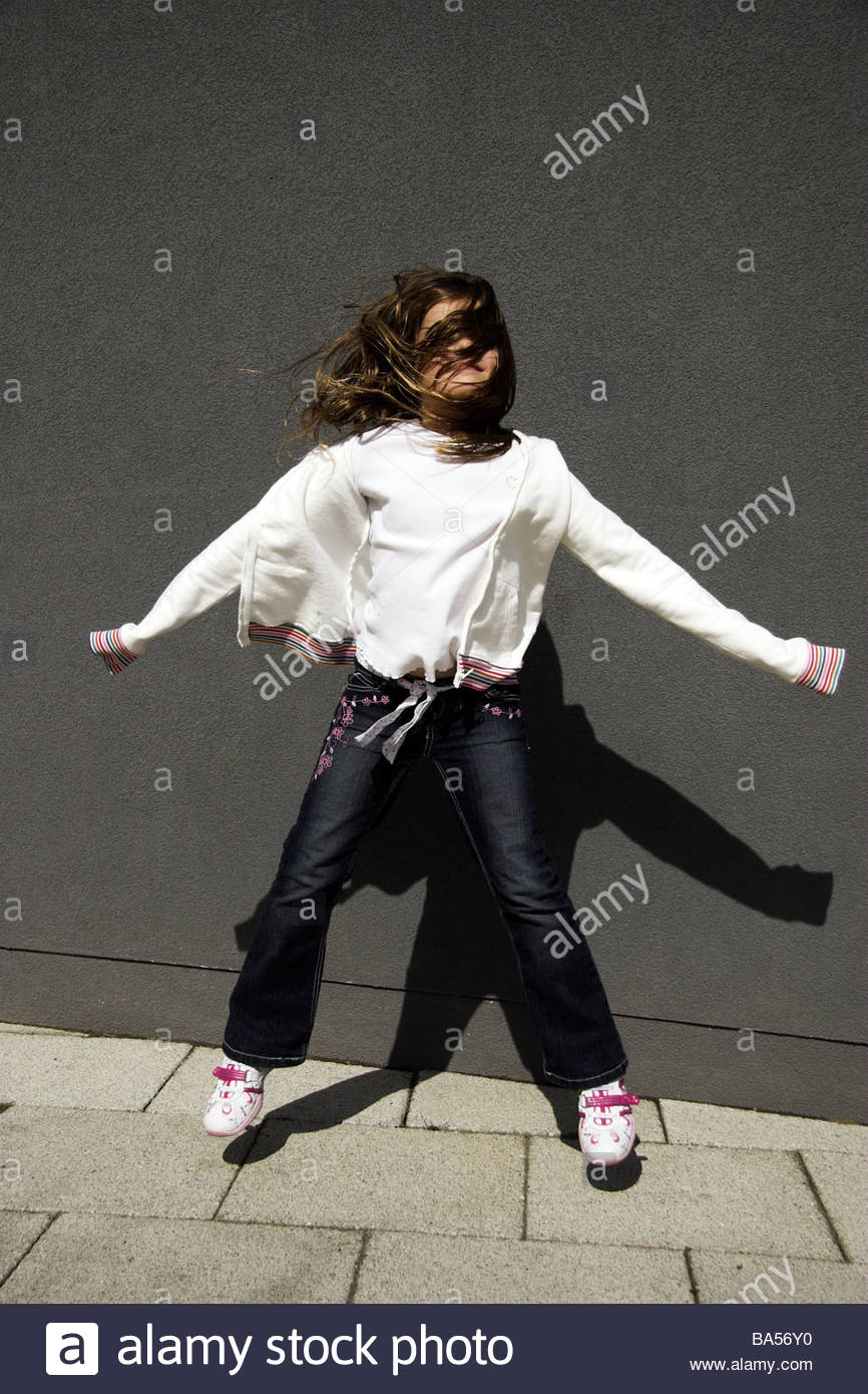 Young girl jumping in the wind, UK. - Stock Image