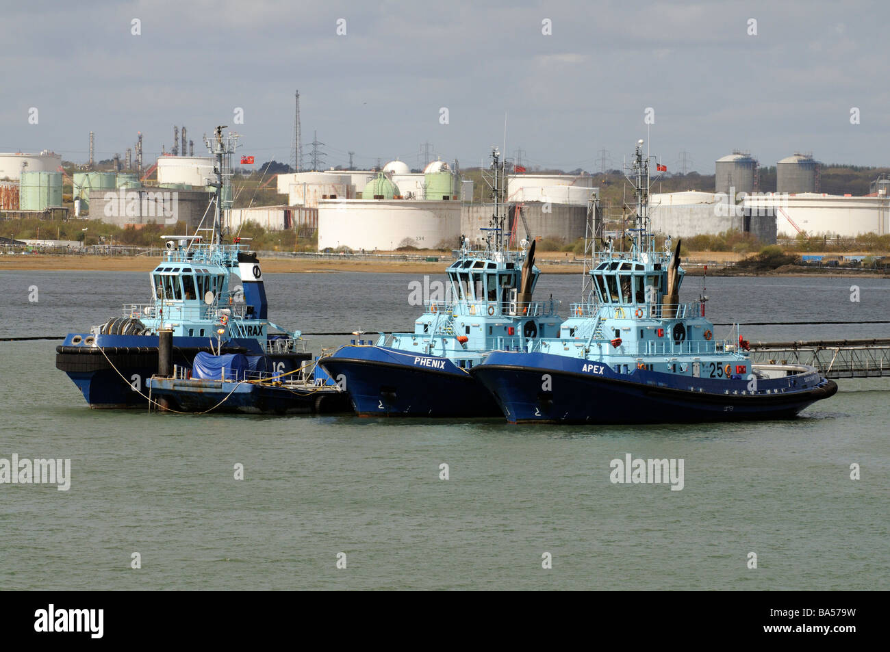 Three ocean going tugs on Southampton Water with a backdrop of the Fawley Refinery storage tanks - Stock Image