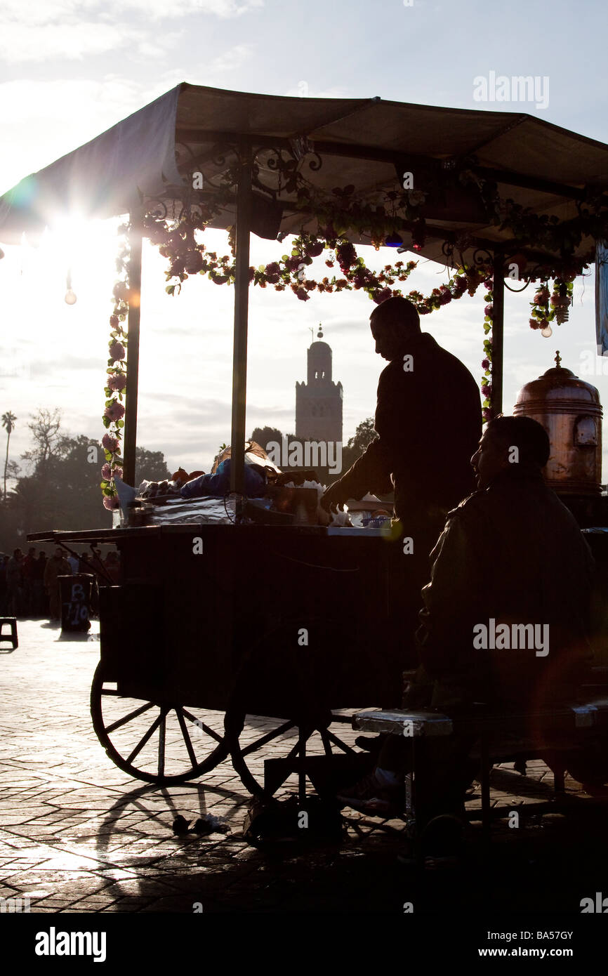 Traditional juice seller stall seen against the sun with koutoubia mosque minaret in background, Jemaa el Fna, Marrakech - Stock Image