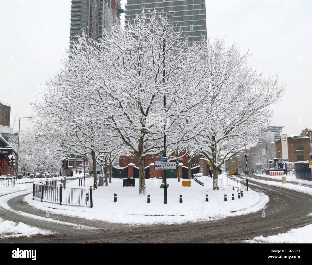 Traffic island nr Heron Quays London UK with Isle of Dogs sign in snow - Stock Image