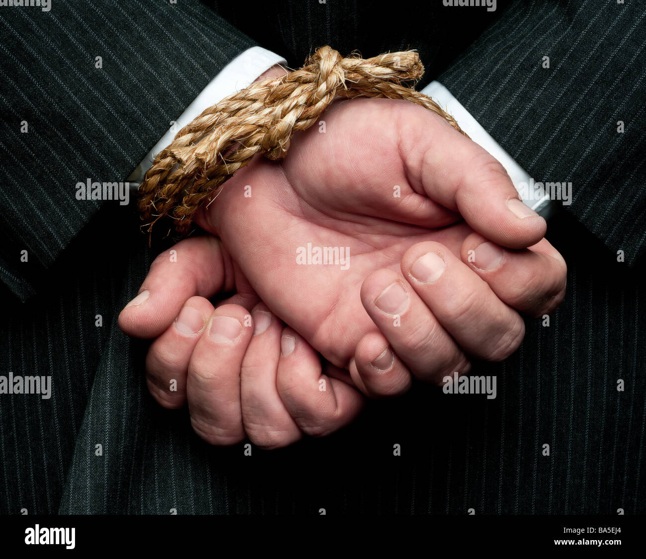 A horizontal view of a business man with his hands tied behind him Concept My hands are tied - Stock Image