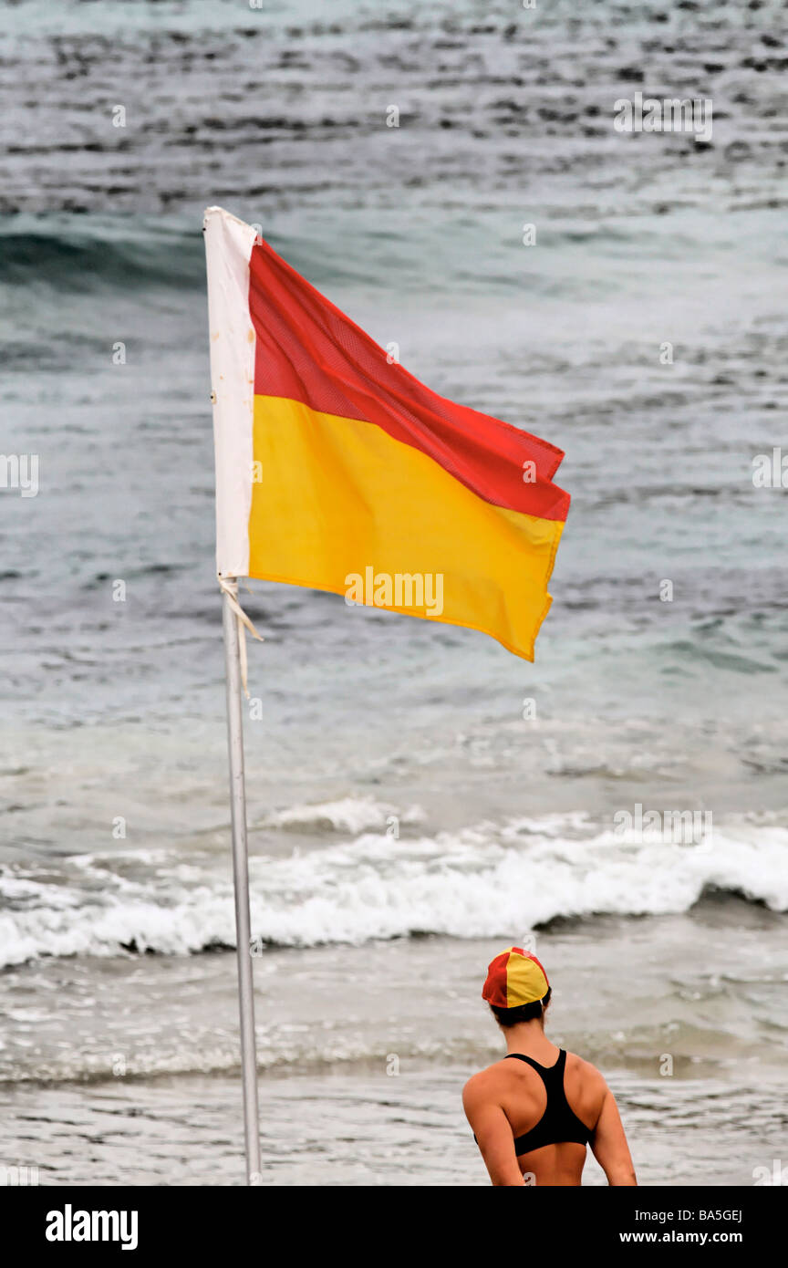 Female Australian Surf Life Saver standing next to a safety flag Port Campbell Victoria - Stock Image