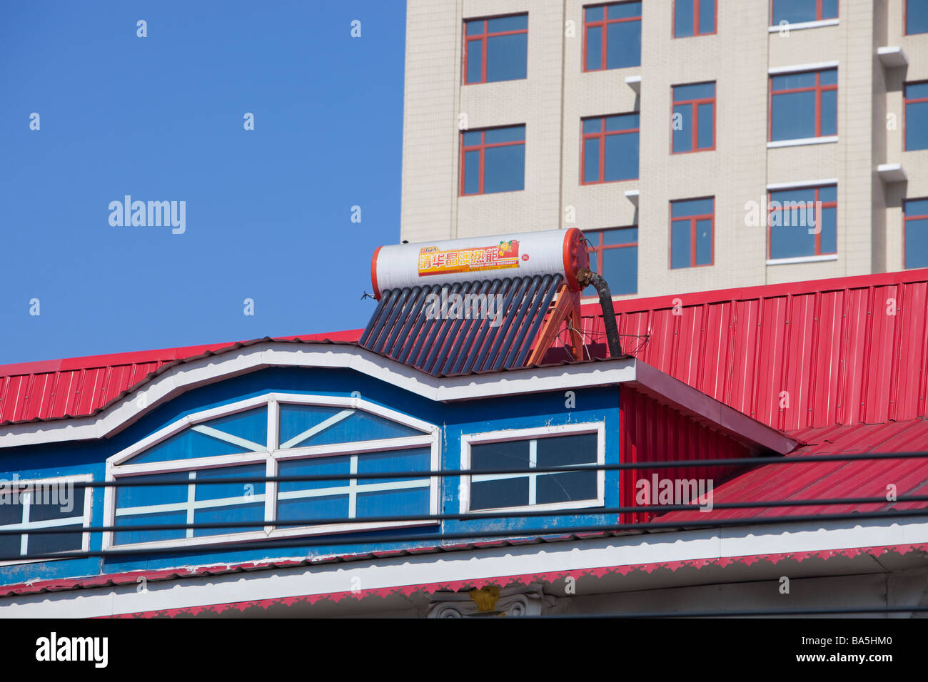 Solar water heaters on the roof of an apartment block in Suihua in northern China - Stock Image