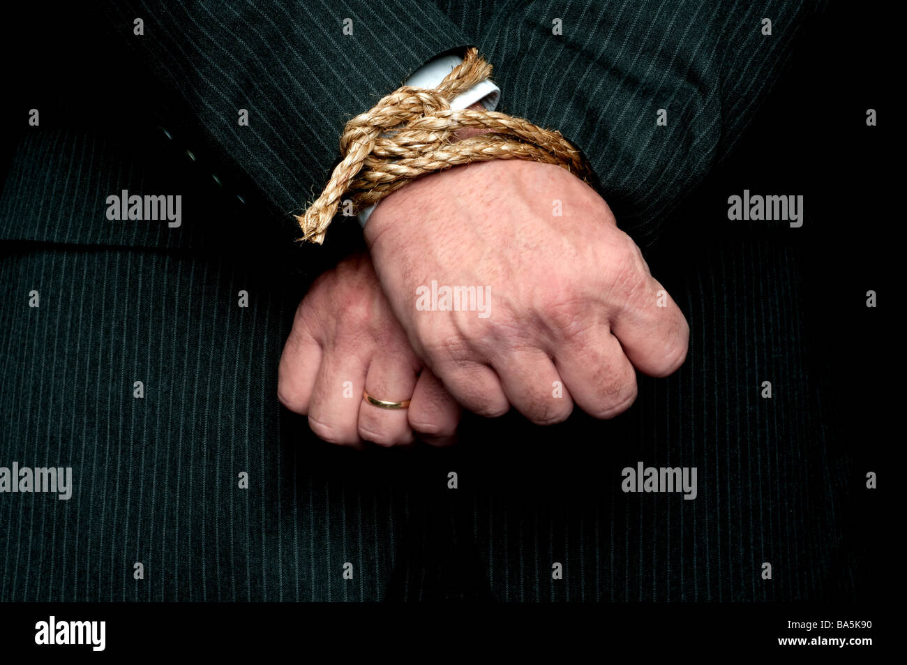 A horizontal view of a business man with his hands tied infront of him Concept My hands are tied - Stock Image