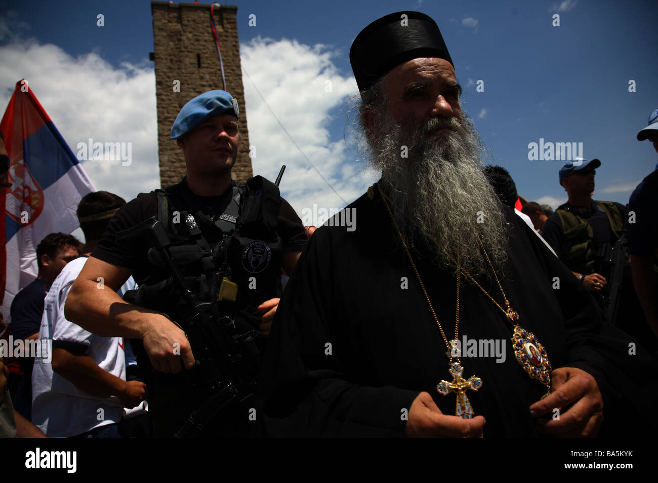 Security force protecting a Serbian Orthodox priest at the Gazimestan monument in Kosovo on the 2007 anniversary - Stock Image
