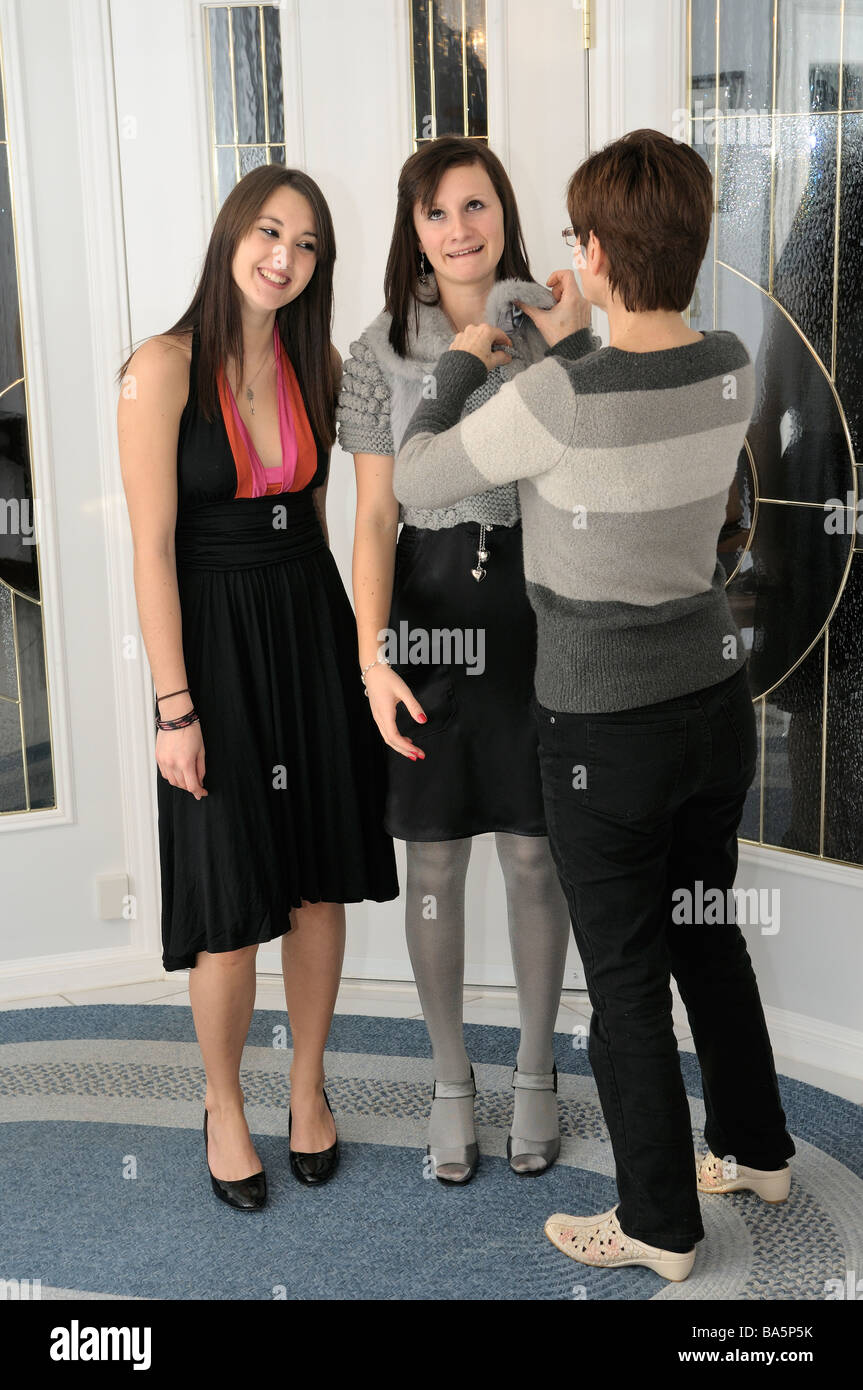 Mother fussing at front door over teen girls getting ready to go out to a semi formal dinner dance - Stock Image
