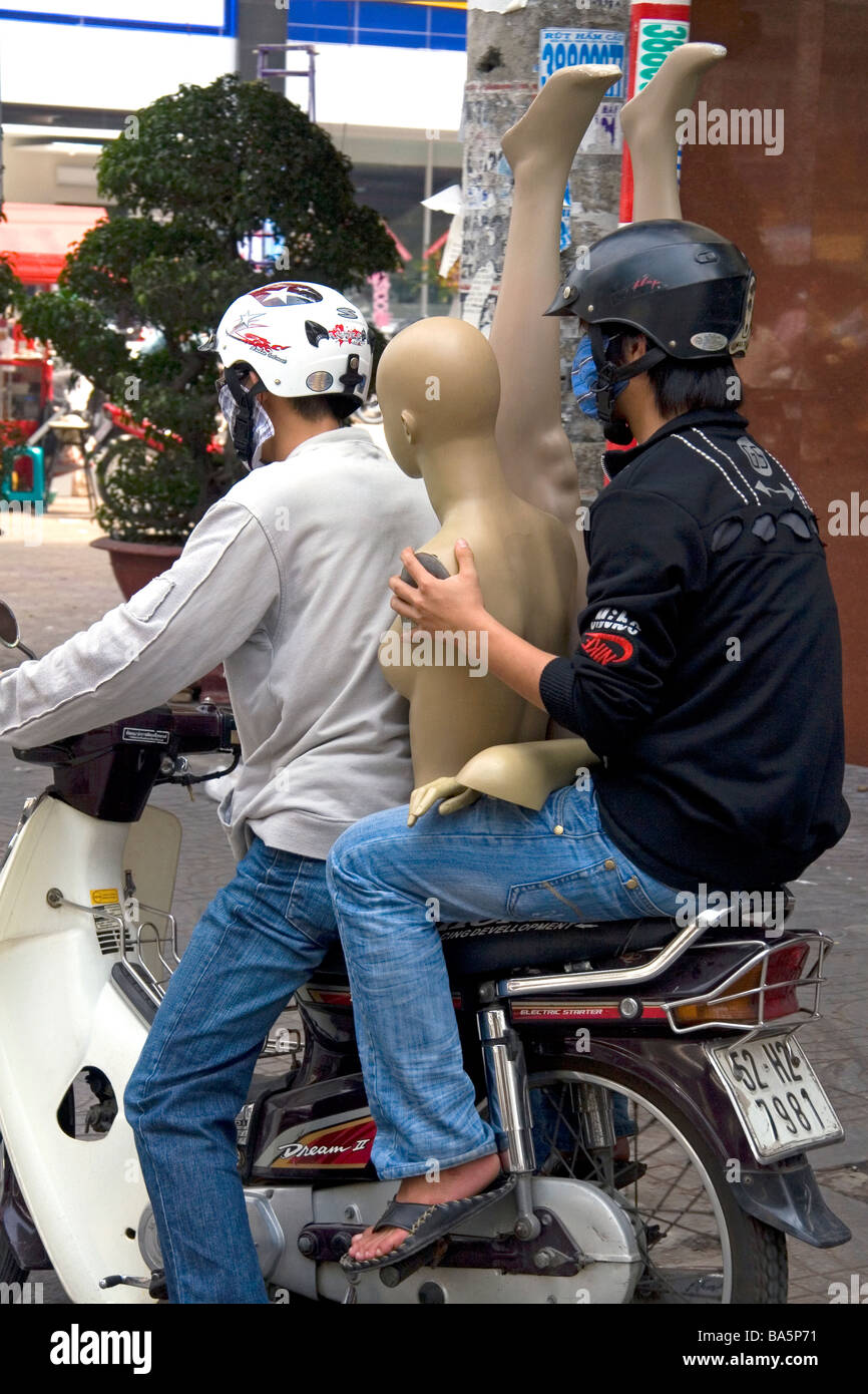 Vietnamese men ride a motorbike with a mannequin in Ho Chi Minh City Vietnam - Stock Image