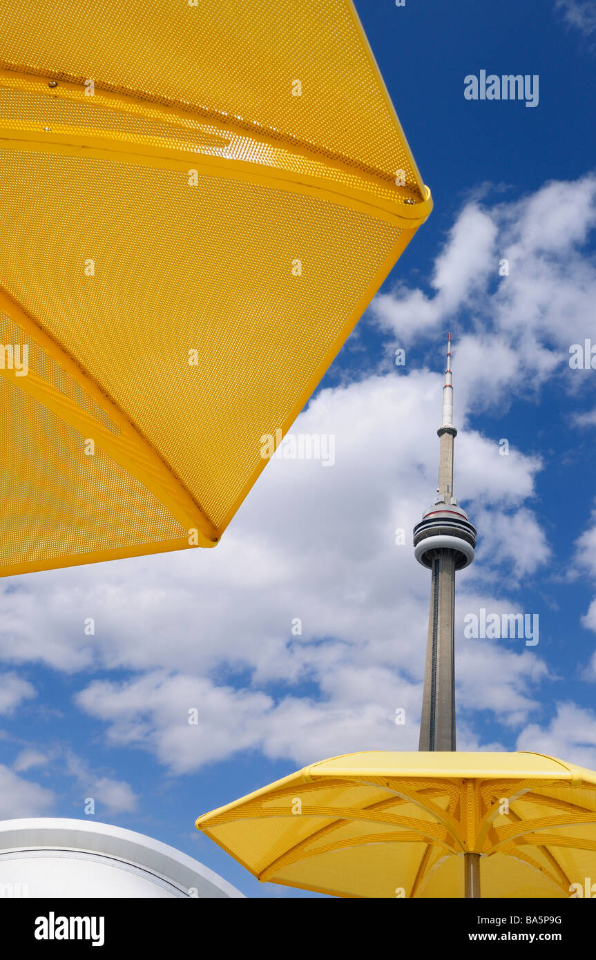 Two yellow metal beach umbrellas at urban beach of HTO Park with CN tower and Rogers Centre Skydome - Stock Image